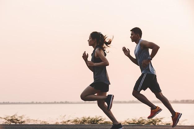 Молодая пара бегун работает на беговой дороге в городском парке