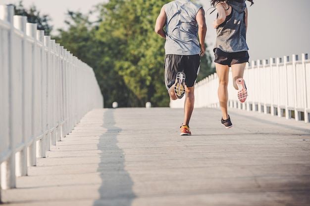 都市公園における道路を走っている若いカップルランナー