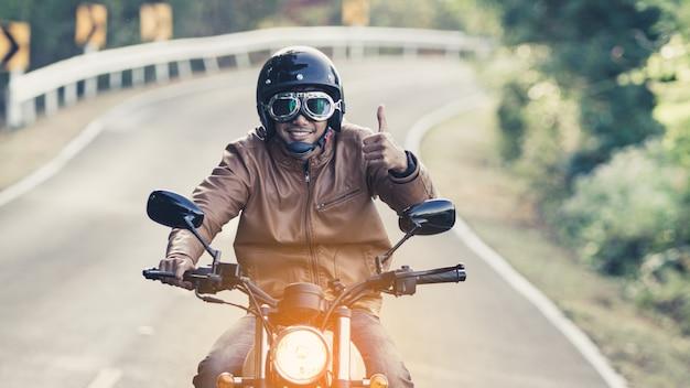 休暇時に自由のライフスタイルで道路にバイクに乗って男