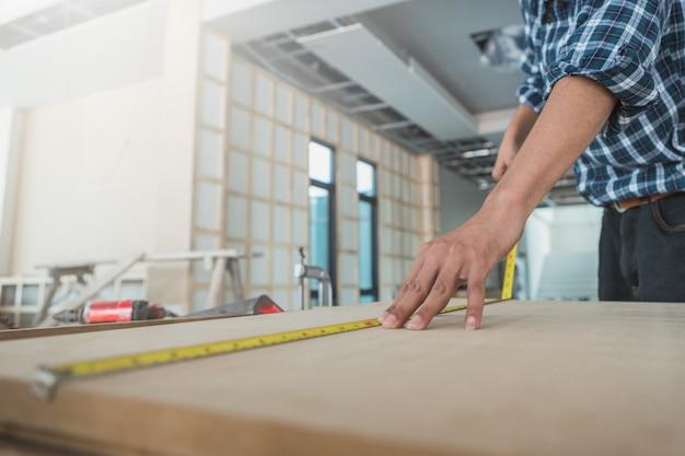 Декоратор работает над дизайном и осматривает фанеру на строительной площадке; декоратор проверяет материал для интерьера