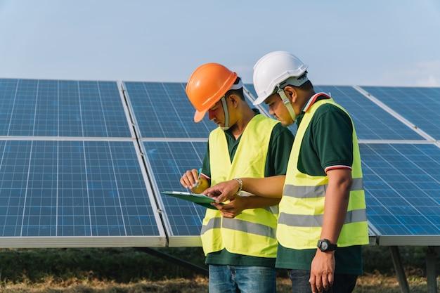 Инженер осматривает солнечную панель на солнечной электростанции