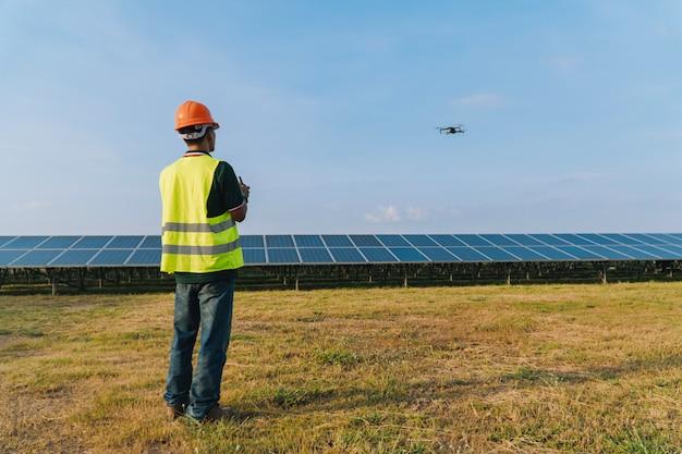太陽光発電所でドローンによるソーラーパネルの検査とチェックを行うエンジニア