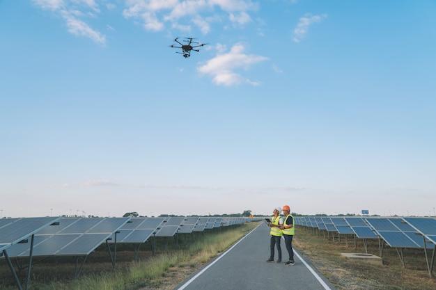 Инспектор инженерной концепции; инженер осматривает солнечную батарею на солнечной электростанции