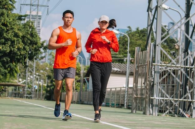 Молодая пара бегун работает на беговой дороге в городском парке; концепция спорта, людей, занятий спортом и образ жизни