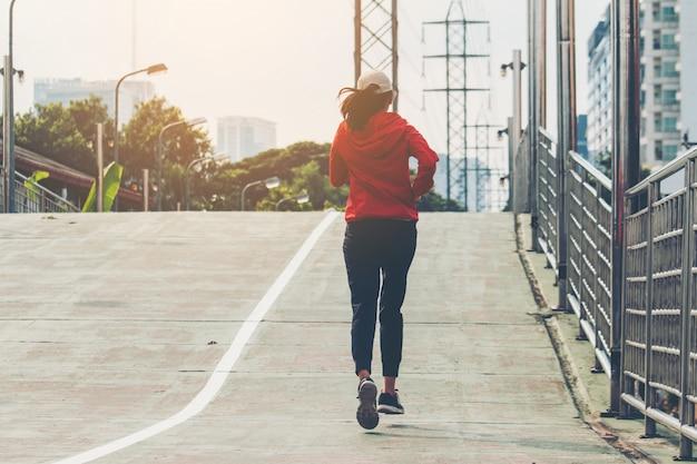 Молодые женщины бегунья по улице бегут на прогулку по городской дороге; спорт, люди, физические упражнения и образ жизни концепция