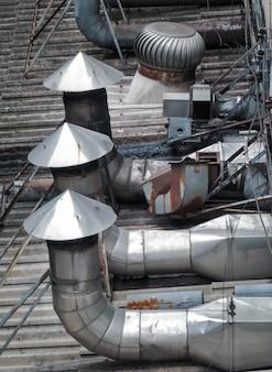 工場の屋根に設置された換気および空調用パイプ