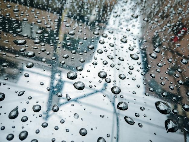 ガラスの背景に雨が降ります。