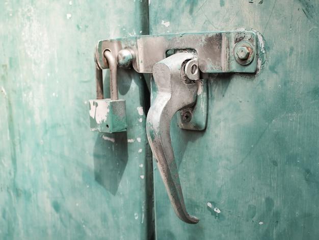緑の古い鋼鉄ドアのロッカーのドアのしみとの扱いをロックします。