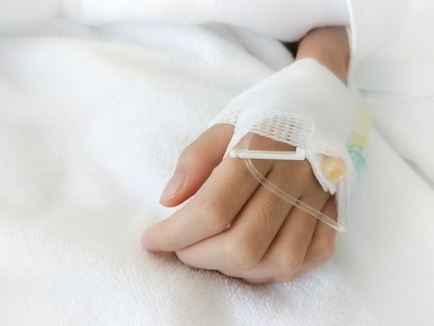 病院での支援のために子供の手がガーゼで包まれています。