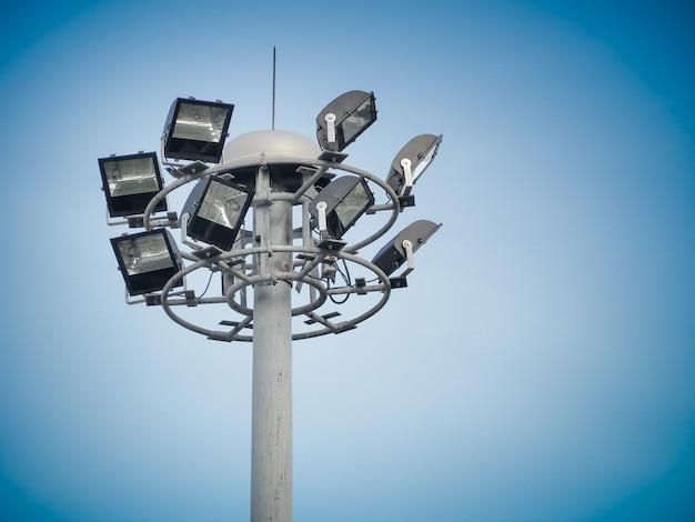 Уличное общественное кольцо светильника с опорой освещения на фоне голубого неба