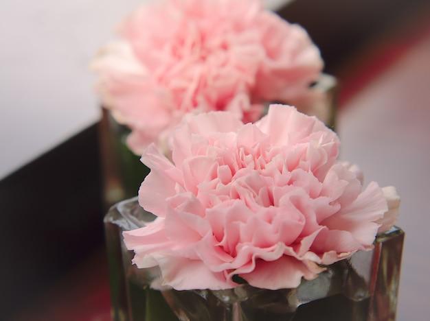 美しいピンクの花のカーネーションやライラックがテーブルの上に飾られます。