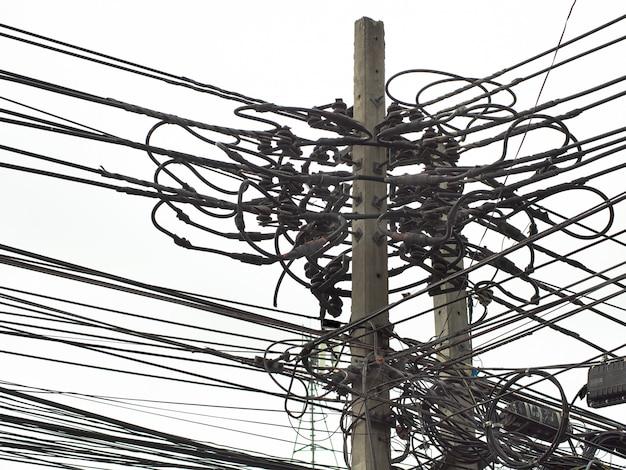 Много электрических кабелей, проводов, телефонных линий и видеонаблюдения на опоре электричества