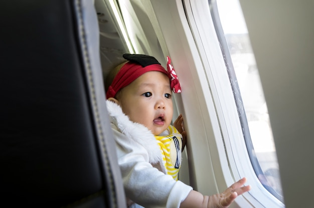 Азиатская девочка, глядя на окно на самолете