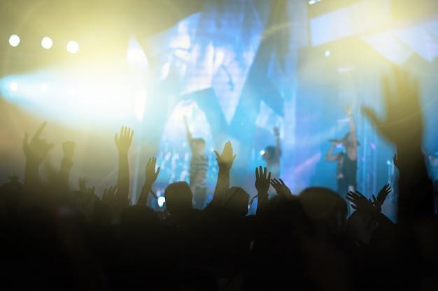 Концертная толпа в силуэтах музыкального фан-клуба с шоу-шоу, в котором участвуют исполнители