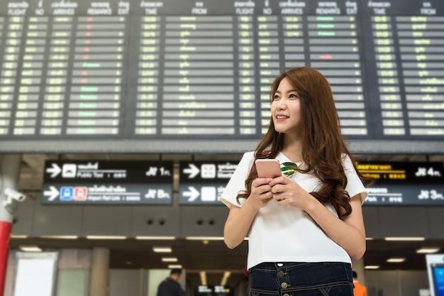 スマートな携帯電話を使った美しいアジアの女性旅行者