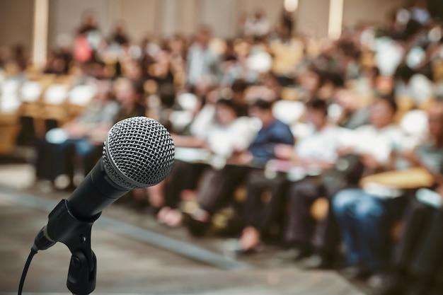 Микрофон над абстрактной размытой фотографией конференц-зала