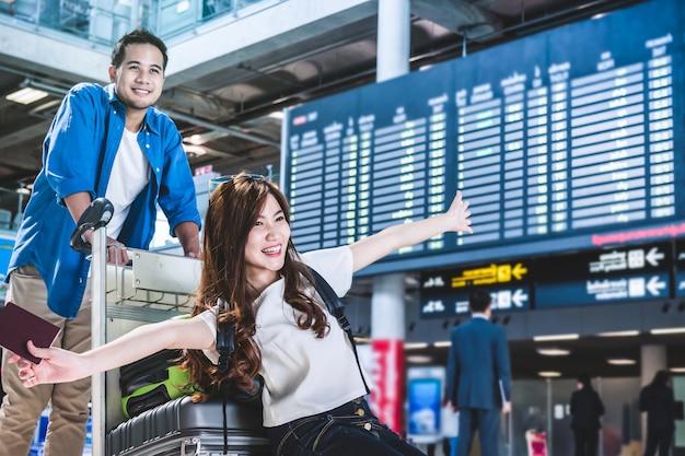 アジアのカップルの旅行者は、空港でスーツケースと