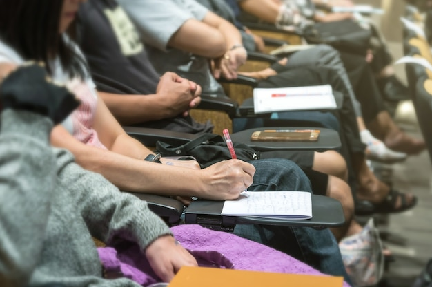 テーブルで紙に書く女性の手のショットを閉じます