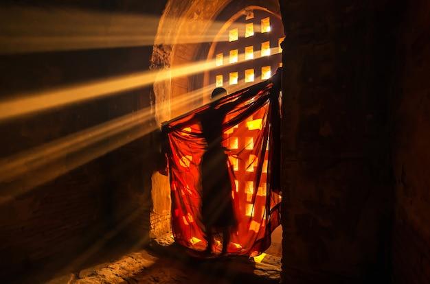 Задняя сторона монаха меняет одежду с солнечным лучом в пагоде в багане
