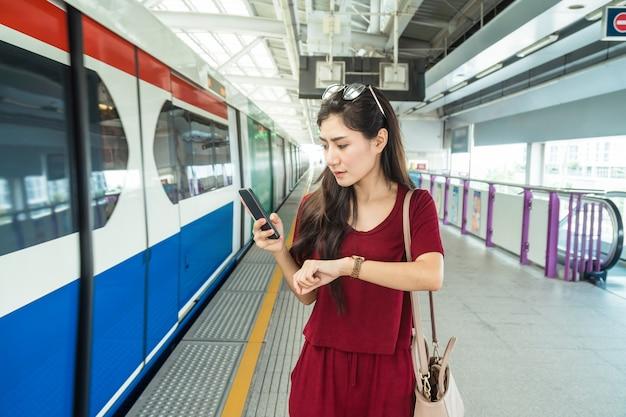 時計を見てカジュアルスーツとアジアの女性の乗客