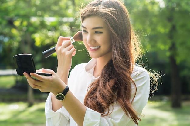 美しいアジアの若い女性の肖像画は、公園で彼女の顔に、