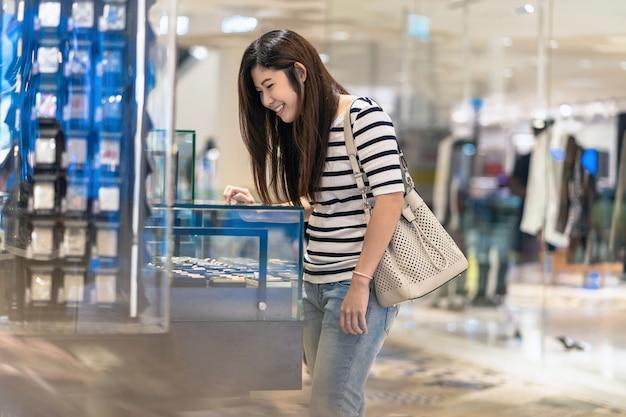 幸せなアジアの女性は、ガラスのキャビンとボーイフレンドまたは夫のための軽いライターを探して