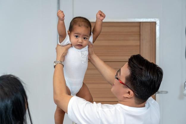 少年の赤ちゃんを保持しているアジアの父親は、家に手と母の手を上げる