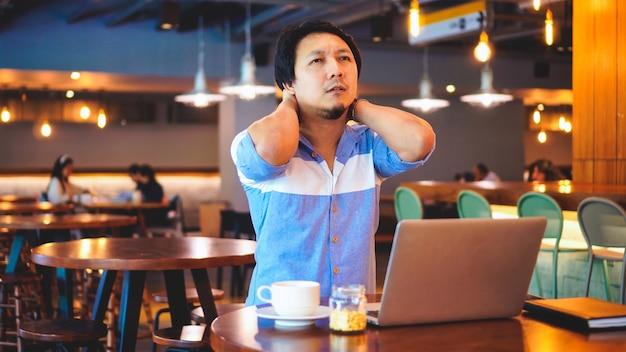症状が現れるカジュアルスーツで働くアジア人のビジネスマンは、首の痛み、腰痛、頭痛