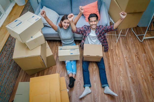 トップビューアジアの若いカップルは、段ボール箱を成功裏に包装した後にうれしいです