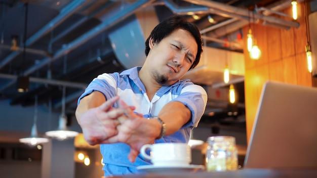 症状を持つカジュアルスーツで働くアジア人のビジネスマンはネックの痛みです