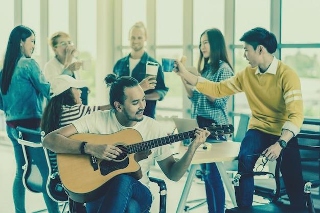 アジア人と多民族のビジネスの人々のグループの上にギターを演奏するアジア人労働者
