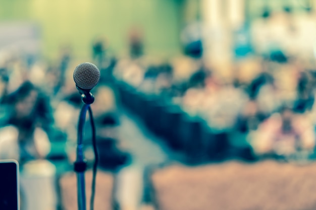 会議ホールやセミナールームの抽象的なぼやけた写真上のマイク