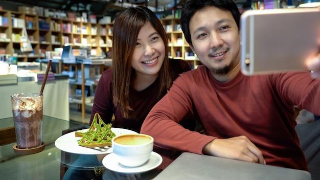現代の喫茶店や職場での幸福行為をセルキーにするアジア人カップル