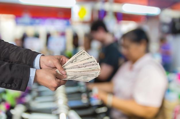 ビジネスマンは抽象的なぼかし写真にお金を提供