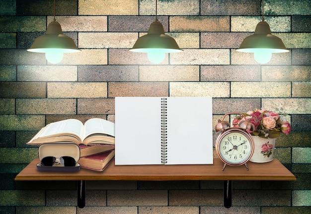 開いた本、目覚まし時計、眼鏡が付いた空のノートブックが付いているトップ木製棚