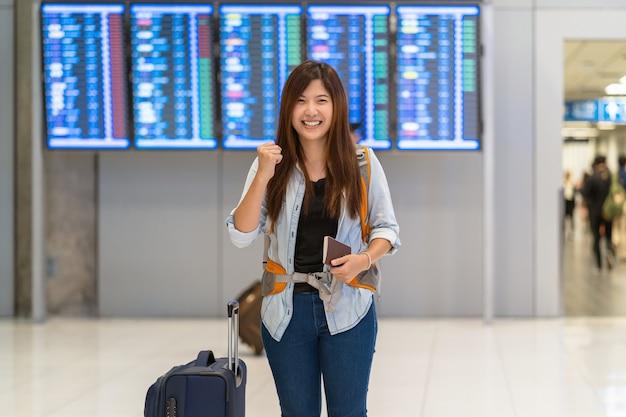 チェックインのためにフライトボードを歩いているパスポート付きの荷物を持っているアジア人の旅行者