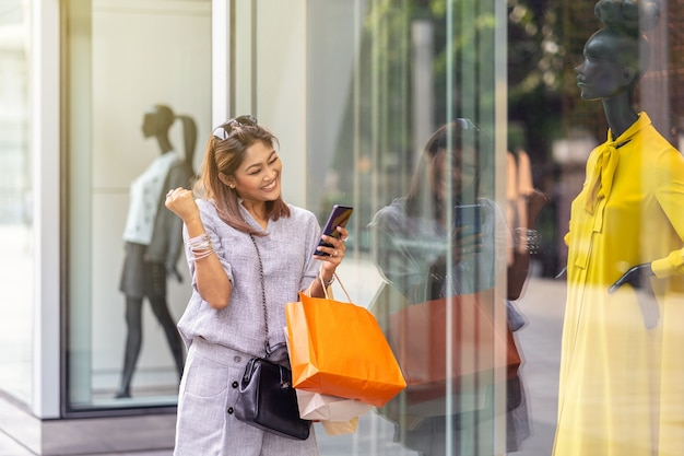 オンラインショッピングの注文を確認するスマートな携帯電話を使用して明るいアジアの女性です