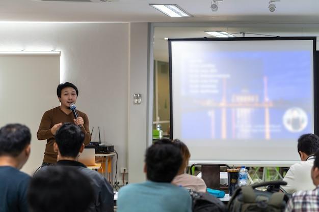 アジアのスピーカーやプレゼンテーションルームの前でステージ上のカジュアルスーツ講義