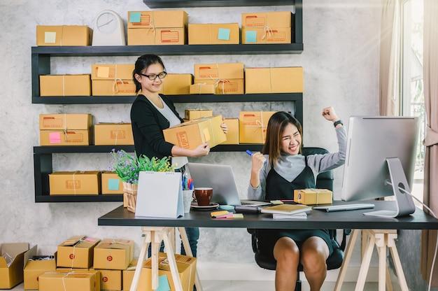 カップルのアジアのティーンエイジャーのオーナーのビジネスマンは、オンラインショッピングのために家で働く