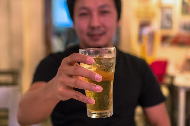 パブの幸福のアクションでアジアの若い男からビールのガラスを保持しているクローズアップの手