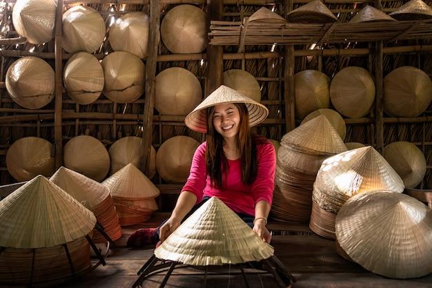 アジアの旅行者女性の職人が伝統的な伝統的なベトナムの帽子を作る