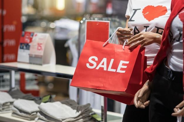 セールスペーパーショッピングバッグを持っているカジュアルな服を着た女性マネキンの一部