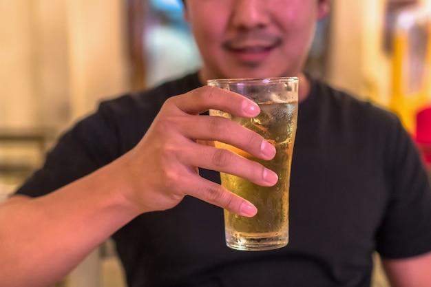 幸せのアクションでアジアの若い男からビールのガラスを保持しているクローズアップの手