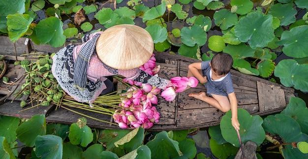 伝統的な木製の船の上でママと遊んでいるベトナムの少年の眺め