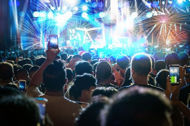 ビデオの記録やライブストリームを取ってモバイルスマートフォンを持っている音楽ファンクラブ手のコンサート群衆
