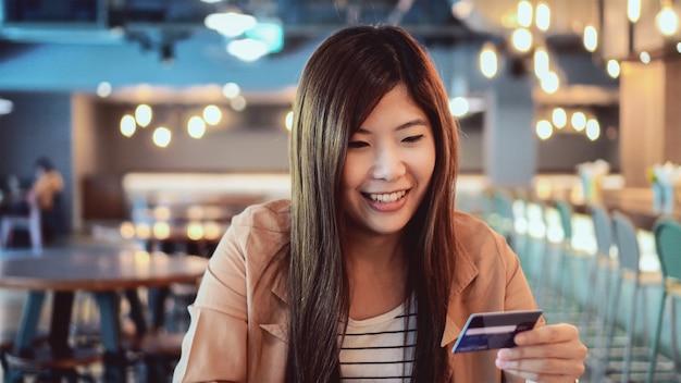 オンラインショッピングのためのコンピューターでクレジットカードを使用してカジュアルなスーツのアジア女性実業家