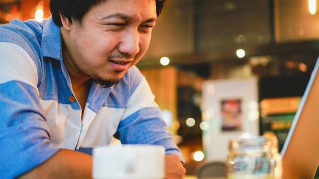 ストレスの感情でコンピューターを操作するカジュアルスーツのアジア系のビジネスマン