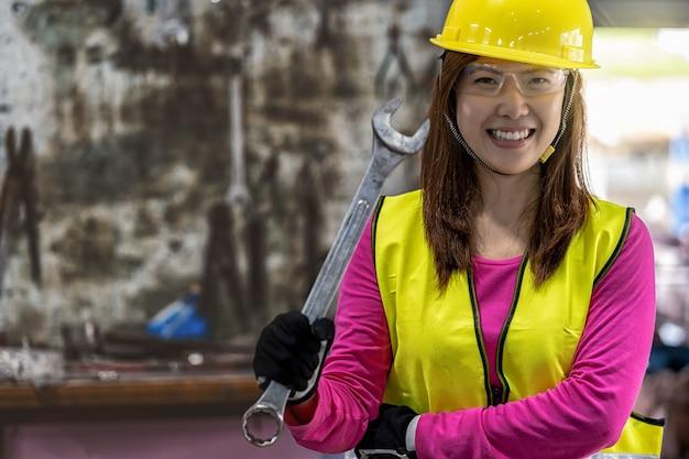 レンチのスタックの上にレンチを保持している安全スーツのアジアの機械工の肖像画