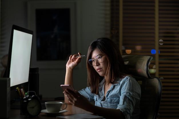 Азиатская коммерсантка сидя и работая усердно на таблице с фронтом настольного компьютера компьютера