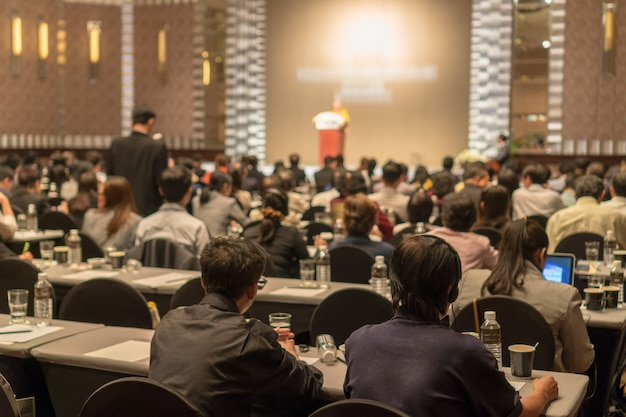 Вид сзади аудитории, носящей и слушающей колонки через гарнитуру переводчика на сцене